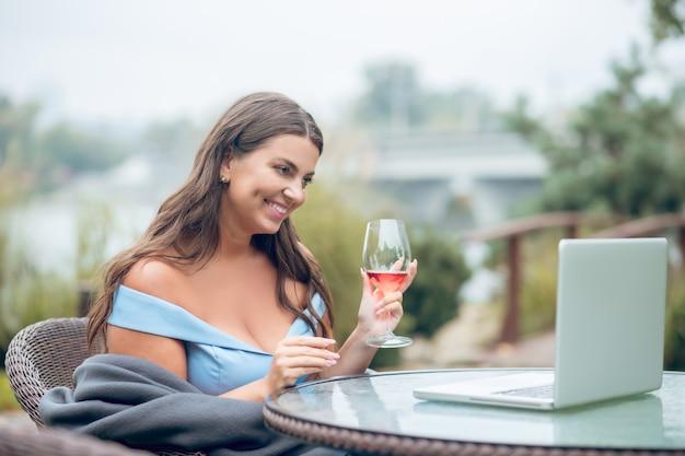 Radosna dość długowłosa kobieta z lampką wina w kratę siedzi przy stole przed laptopem w kawiarni na świeżym powietrzu