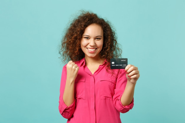 Radosna dziewczyna afryki w ubranie robi gest zwycięzcy trzymać karty kredytowej banku na białym tle na tle niebieskiej ściany turkus w studio. ludzie szczere emocje, koncepcja stylu życia. makieta miejsca na kopię.