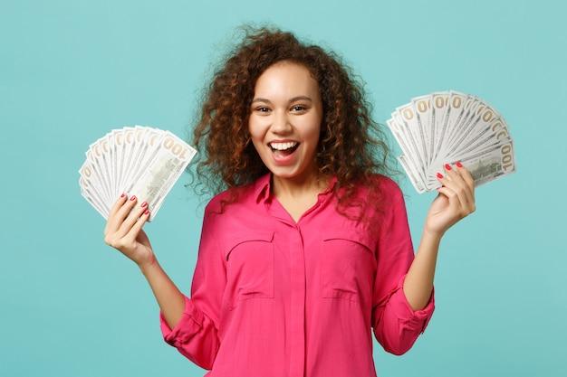 Radosna dziewczyna afryki w ubranie trzyma wentylator pieniędzy w banknotach dolara, pieniądze w gotówce na białym tle na tle niebieskiej ściany turkus. ludzie szczere emocje, koncepcja stylu życia. makieta miejsca na kopię.