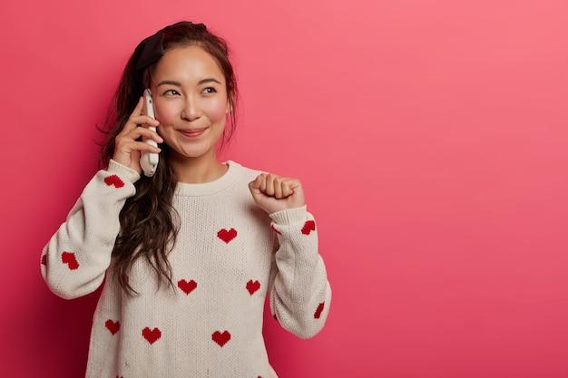 Radosna dziewczyna lubi luźną, przyjacielską rozmowę z kumplem, rozmawia i raduje się z fajnych wiadomości, patrzy na bok z rozmarzonym wyrazem twarzy, podnosi zaciśniętą pięść, trzyma smartfon przyciśnięty do ucha.