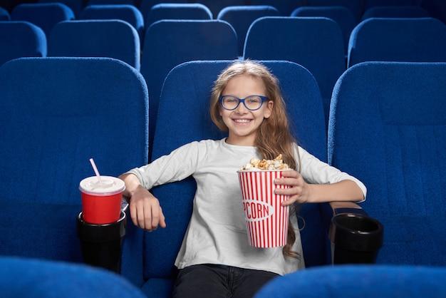 Radosna dziewczyna trzyma wiadro popcornu, pozowanie w kinie.