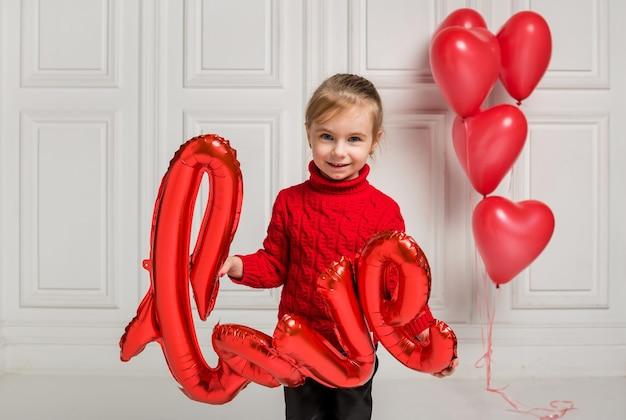 Radosna dziewczyna w czerwonym swetrze siedzi na podłodze i trzyma czerwone balony na białym tle z miejscem na tekst
