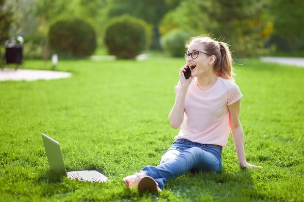 Radosna dziewczyna w okularach rozmawia przez telefon w parku