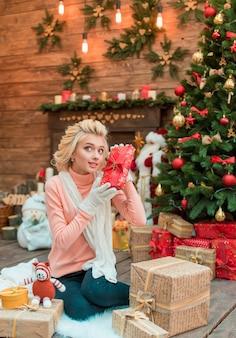 Radosna dziewczyna w zimowe ubrania, siedząc obok choinki, trzymając pudełko.