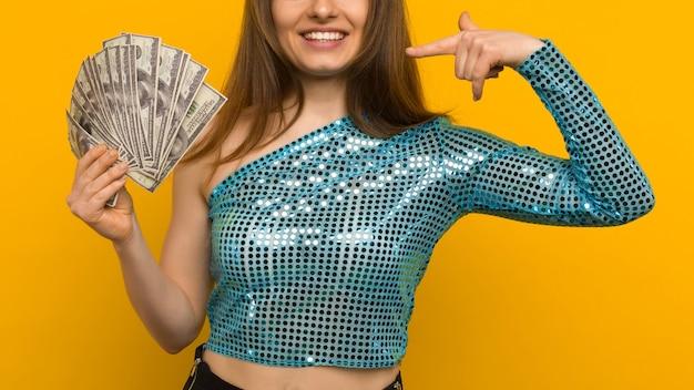 Radosna dziewczyna wygrała na loterii i wskazała na wachlarza dolarów w dłoniach na żółtym tle - obrazek