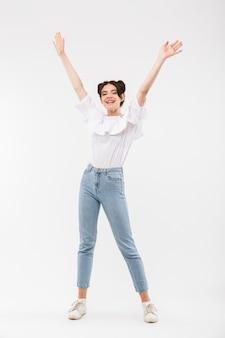 Radosna dziewczyna z fryzurą double buns śmiejąc się i zabawy podnosząc ramiona, na białym tle