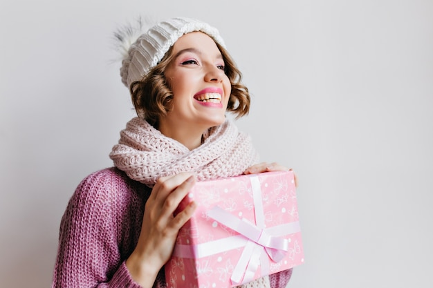 Radosna dziewczyna z krótką fryzurą ciesząca się ferie zimowe z prezentami. kryty portret pięknej młodej kobiety w sweter i szalik, trzymając prezent na nowy rok na białej ścianie.