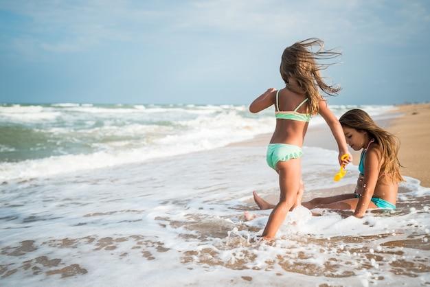 Radosna dziewczynka cieszy się dniem na plaży, relaksując się na morzu w słoneczny, ciepły letni dzień