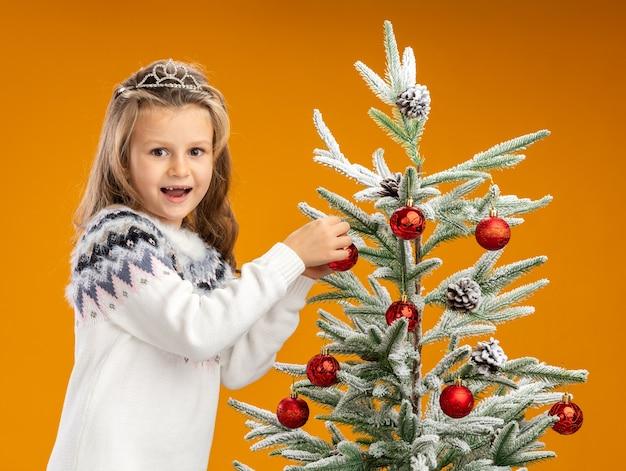 Radosna dziewczynka stojąca w pobliżu choinki ubrana w tiarę z girlandą na szyi trzyma drzewo na pomarańczowej ścianie