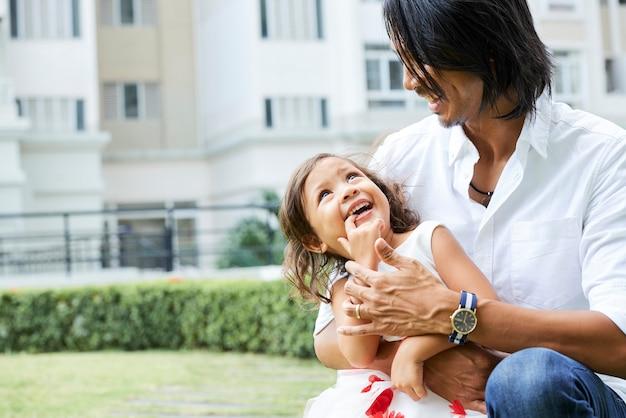 Radosna dziewczynka wkłada palec do ust i patrzy na ojca, który ją przytula