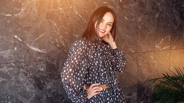 Radosna elegancka brunetka w długiej szarej sukience w kropki pozuje uśmiechając się i kręci pokazując sukienkę w pobliżu marmurowej ściany, światło słoneczne