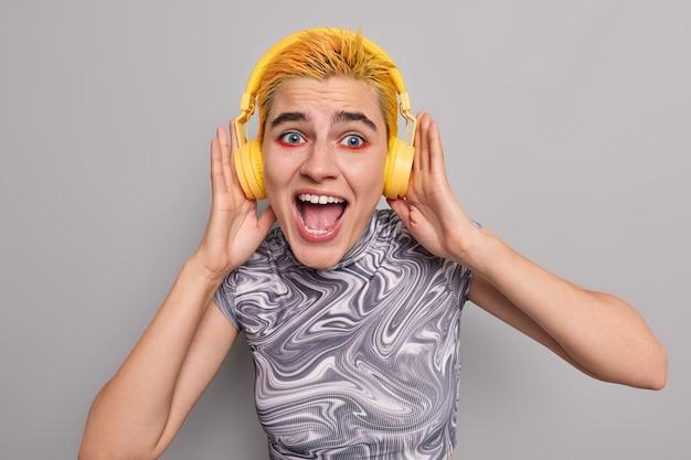 Radosna emo dziewczyna ma stylową fryzurę jasny żywy makijaż krzyczy głośno słucha muzyki z głośnym dźwiękiem spędza wolny czas na ulubionym hobby odizolowanym od szarej ściany