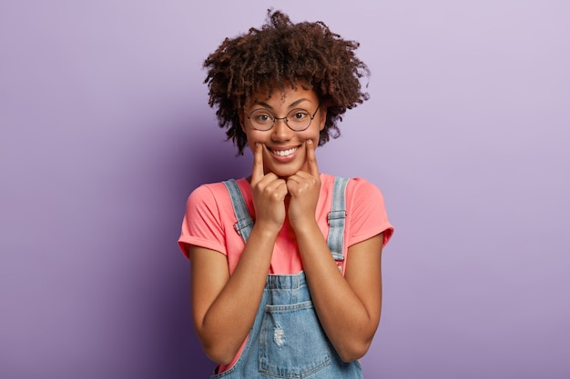 Radosna etniczna kobieta trzyma przednie palce w kącikach ust, uśmiecha się szeroko, udaje, że jest w dobrym nastroju, zapomina o wszelkich kłopotach, nosi okrągłe okulary korekcyjne, ubrana swobodnie