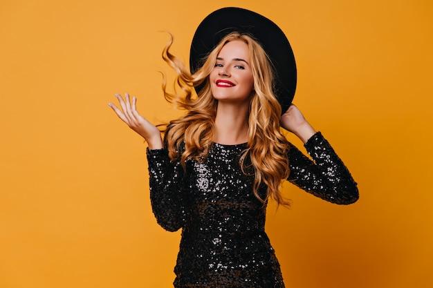 Radosna europejska dziewczyna z długimi fryzurami wyrażająca szczęście. emocjonalna jasnowłosa kobieta pozuje na żółtej ścianie.