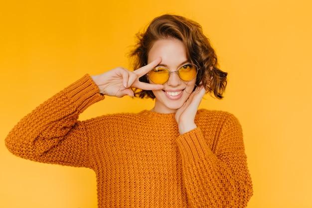 Radosna europejska kobieta z błyszczącymi lokami, śmiejąca się i pokazująca znak pokoju na żółtym tle