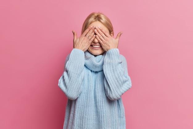 Radosna figlarna kobieta ukrywa oczy dłońmi, uśmiecha się wesoło i czeka na wyjątkową chwilę lub niespodziankę