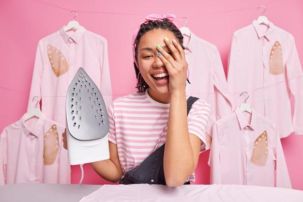 Radosna gospodyni sprawia, że twarz dłoni uśmiecha się radośnie zajęta prasowaniem ubrań w domu pozuje przy desce trzyma elektryczne żelazko parowe różowa ściana