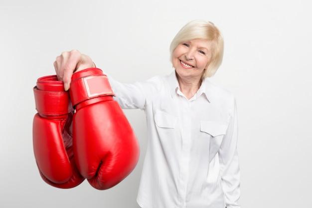 Radosna i miła staruszka trzyma w prawej ręce rękawice bokserskie i uśmiecha się. na emeryturze ma co robić.