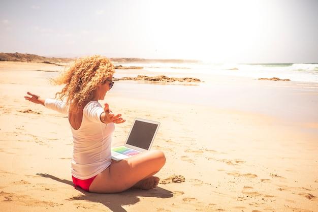 Radosna i szczęśliwa praca związana z młodymi nowoczesnymi ludźmi pracującymi poza biurem na świecie - piękna kobieta sukcesu z laptopem podłączonym na plaży z widokiem na morze
