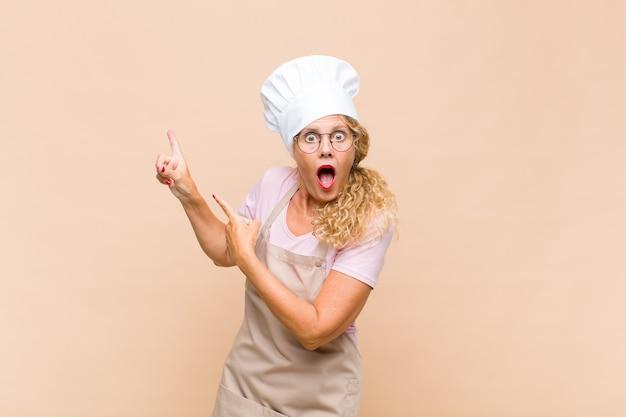 Radosna i zdziwiona piekarz w średnim wieku, uśmiechnięta ze zszokowanym wyrazem twarzy i wskazująca w bok
