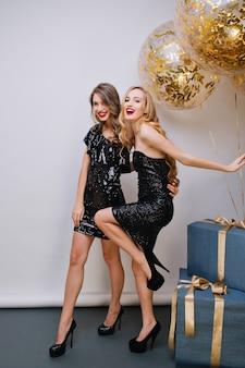 Radosna jasnowłosa kobieta zabawnie tańczy obok niebieskich pudełek i patrząc z uśmiechem. wewnątrz portret dwóch uroczych dziewczyn spędzających razem czas podczas przyjęcia urodzinowego.