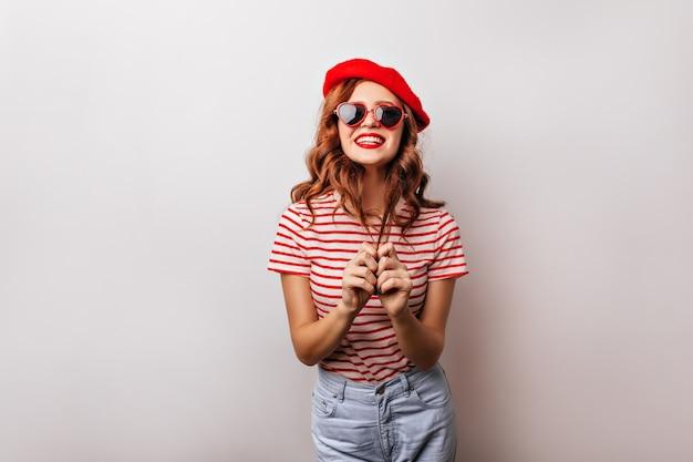 Radosna kaukaska dziewczyna w berecie chłodzi. wyrafinowana francuska kobieta w okularach przeciwsłonecznych pozuje z uśmiechem.