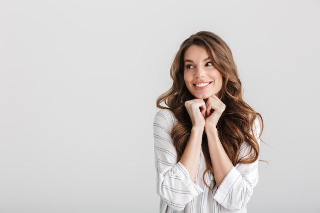 Radosna kaukaska kobieta patrząca na bok i śmiejąca się na białym tle na białym tle