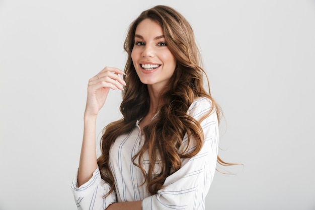 Radosna kaukaska kobieta pozuje i śmieje się z kamery na białym tle na białym tle