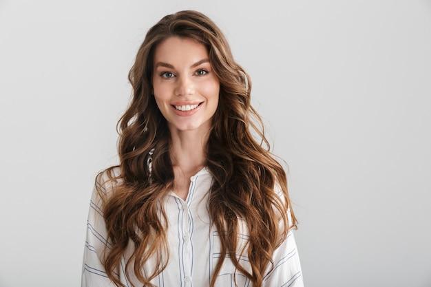 Radosna kaukaska kobieta uśmiecha się i patrzy na kamerę odizolowaną na białym tle