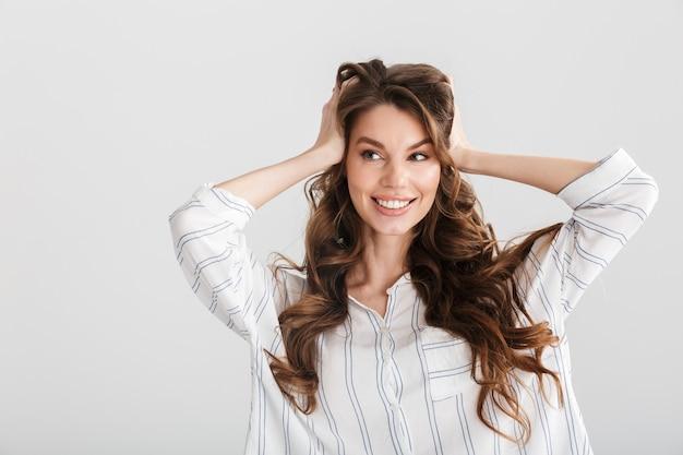 Radosna kaukaska kobieta uśmiechająca się i chwytająca za głowę odizolowana na białym tle