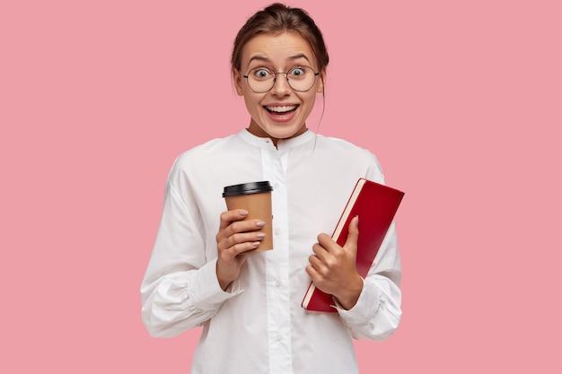Radosna kaukaska młoda dziewczyna w białych ubraniach, trzyma aromatyczną kawę na wynos i książkę