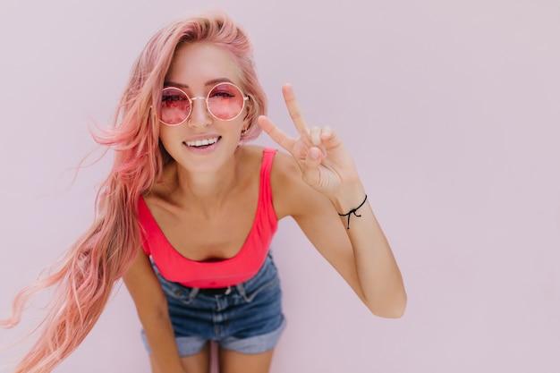 Radosna kaukaski kobieta z różowymi włosami pozuje z uroczym uśmiechem.