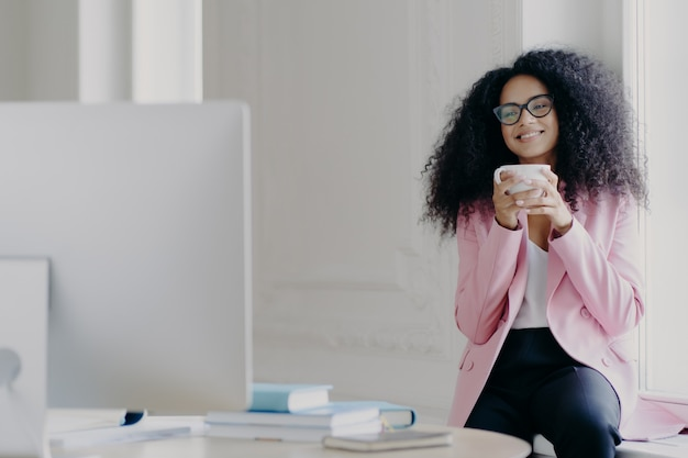 Radosna kędzierzawa kobieta freelancer ma przerwę na kawę, trzyma biały kubek z napojem