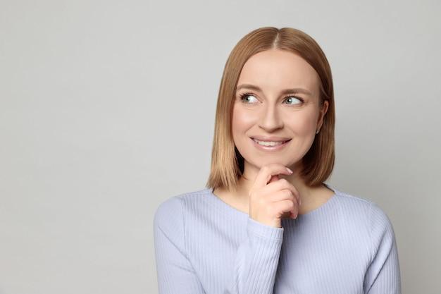 Radosna kobieta dotyka podbródka i spogląda na puste miejsce na kopię produktu, myśląc o ofercie handlowej, przyjemnie się uśmiecha
