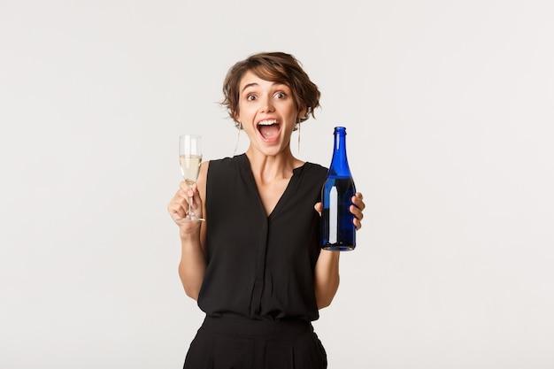 Radosna kobieta korzystających ze strony, trzymając butelkę i kieliszek szampana, stojąc nad białym.