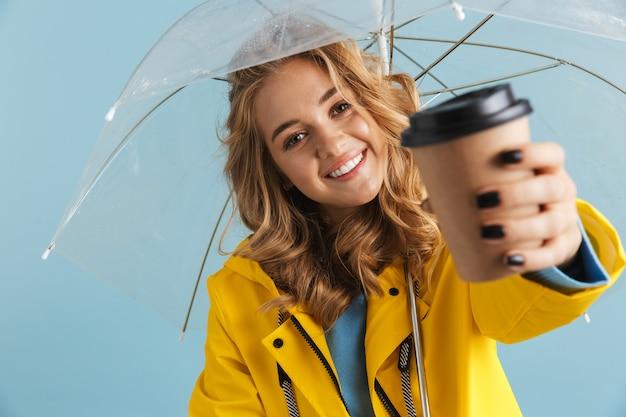 Radosna kobieta lat dwudziestych ubrana w żółty płaszcz przeciwdeszczowy stojąca pod przezroczystym parasolem z kawą na wynos