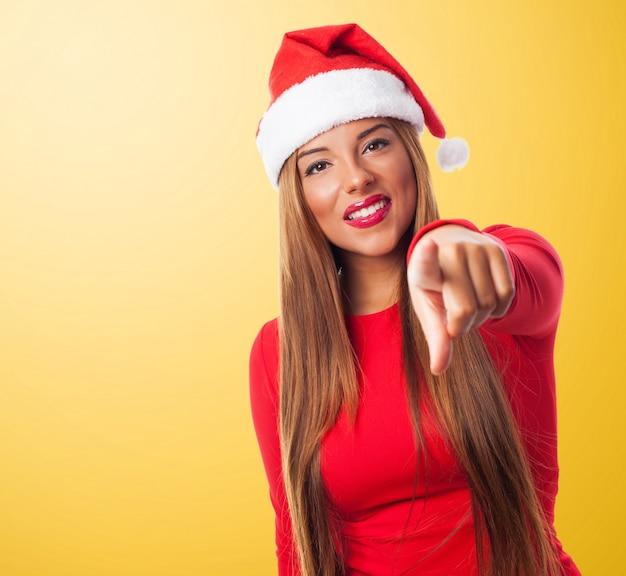 Radosna kobieta ma na sobie kapelusz santa wskazując na ciebie