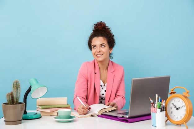 Radosna kobieta myśli i robi notatki w pamiętniku podczas pracy przy biurku odizolowanym nad niebieską ścianą