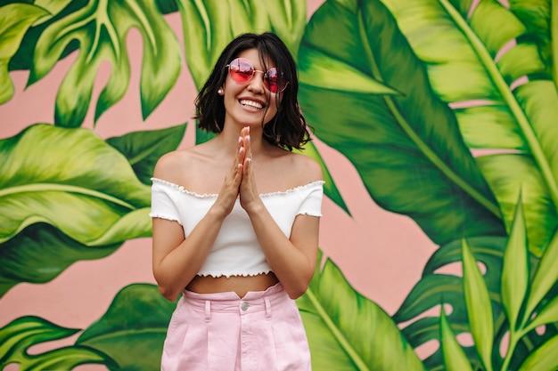 Radosna kobieta pozuje ze szczerym uśmiechem w pobliżu graffiti