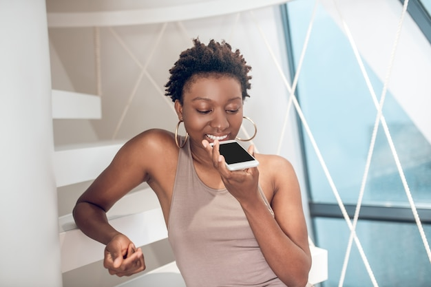 Radosna kobieta robi wiadomość głosową na smartfonie
