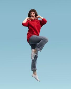 Radosna kobieta skoki na białym tle na niebiesko