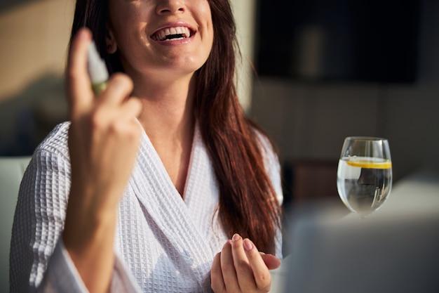 Radosna kobieta spryskuje twarz przed zrobieniem makijażu