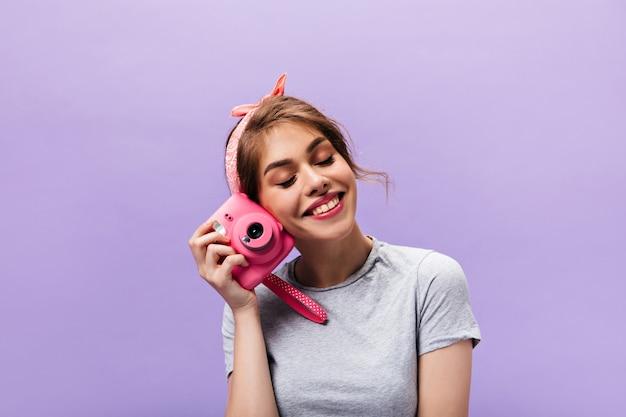 Radosna kobieta szczęśliwie pozuje z różowym aparatem. całkiem jasna dziewczyna w szarej koszulce i letniej opasce uśmiechnięta na fioletowym tle.