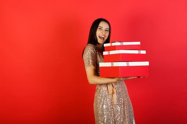 Radosna kobieta trzyma dużo pudełek z prezentami na czerwonym tle.