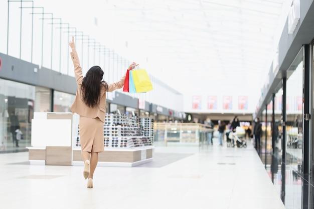 Radosna kobieta trzyma na górze papierowe torby z zakupami w centrum handlowym