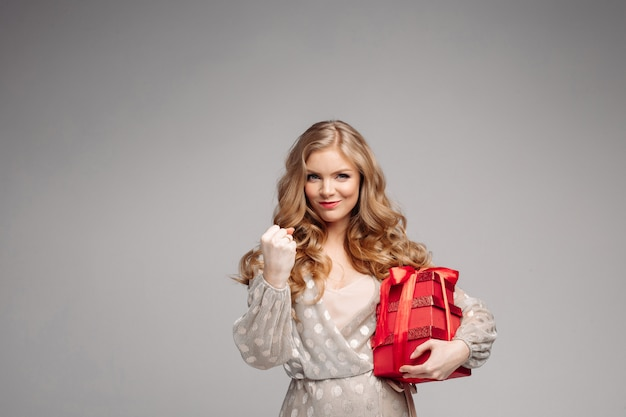 Radosna kobieta trzyma wiele pudeł z prezentami.