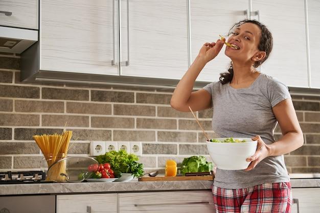 Radosna kobieta trzymająca w rękach miskę sałatki warzywnej i gryząca pierścień pieprzu.