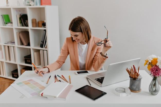 Radosna kobieta w brzoskwiniowej marynarce z uśmiechem przegląda dokumenty, siedząc w wygodnym, jasnym biurze.