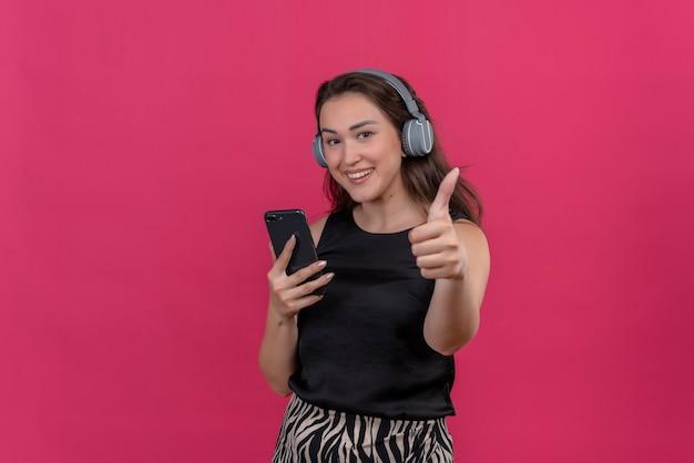 Radosna kobieta w czarnym podkoszulku słucha muzyki ze słuchawek i kciukiem na różowej ścianie