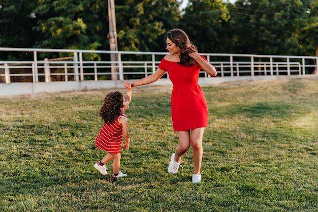 Radosna kobieta w czerwonej sukience tańczy z córką na trawniku. pełnometrażowy odkryty portret brunetki i małego dziecka, zabawy w parku.
